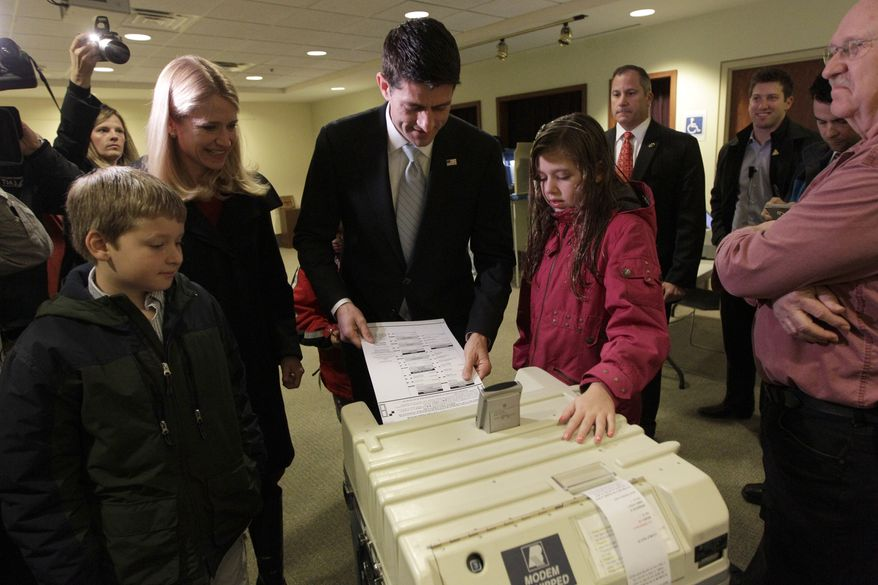 Rep. Paul Ryan, the Republican vice presidential candidate, casts his ballot as wife Janna, son Charlie (left) and daughter Liza watch on Tuesday, Nov. 6, 2012, at the Hedberg Public Library in Janesville, Wis. (AP Photo/Mary Altaffer)