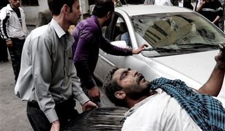 This photo released by the Syrian official news agency SANA, shows a Syrian man helping an injured man at the scene after a blast occurred according to footage and reports shown on State-run Al-Ikhbariya television in the Mazzeh al-Jabal district of the Syrian capital Damascus, Syria, Monday, Nov. 5, 2012. Several people were killed and injured, among them children, Al-Ikhbaria said. (AP Photo/SANA)