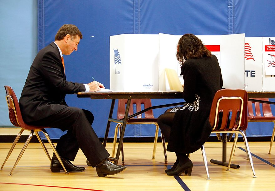 George Allen, U.S. Senate candidate in Virginia, and his wife, Susan, vote at Washington Mill Elementary School in Alexandria, Va., on Nov. 6, 2012. (Eva Russo/Special to The Washington Times)