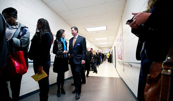 George Allen, U.S. Senate candidate in Virginia, and his wife, Susan, wait in line to vote at Washington Mill Elementary School in Alexandria, Va., on Nov. 6, 2012. (Eva Russo/ Special to The Washington Times)