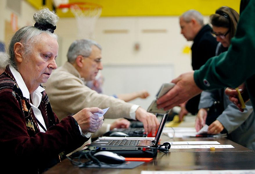 Election officers check voters' identification at Washington Mill Elementary School in Alexandria, Va., on Nov. 6, 2012. (Eva Russo/Special to The Washington Times)