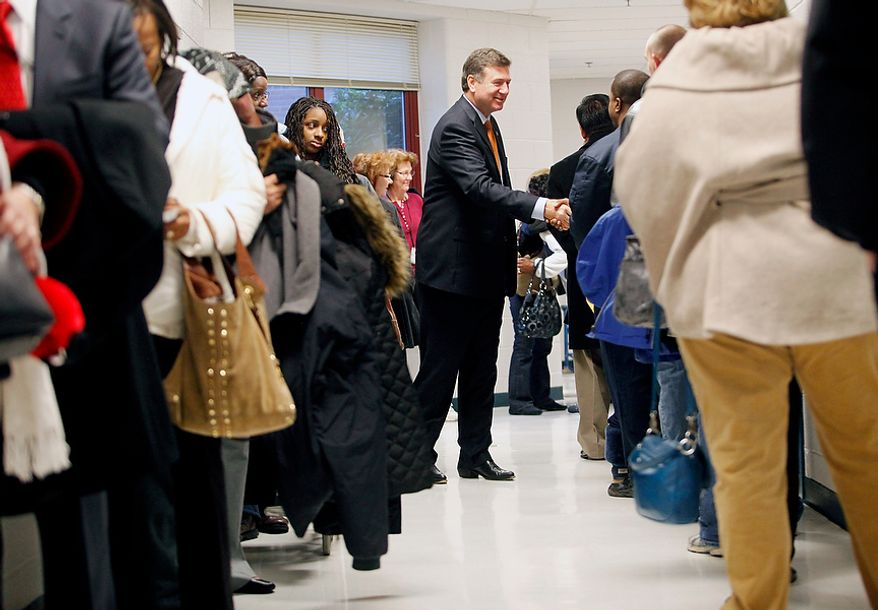 George Allen, U.S. Senate candidate in Virginia, greets voters as they wait in line at Washington Mill Elementary School in Alexandria, Va., on Nov. 6, 2012. Allen was also there to vote with his wife, Susan. (Eva Russo/Special to The Washington Times)