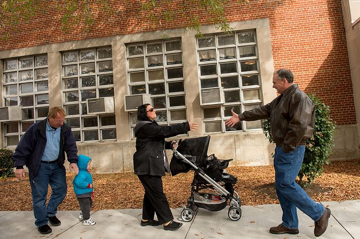 Michael and Laura Macario [cq] and their grandson Maxwell, 2, are greeted by Democratic candidate for Senate Tim Kaine, right, as they arrive to vote outside the polling entrance to G.W. Carver Elementary School on election day morning, Richmond, Va., Tuesday, November 6, 2012. (Andrew Harnik/The Washington T