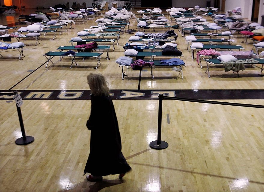 A voter walks through a makeshift shelter in a gymnasium at Toms River East High School on Tuesday, Nov. 6, 2012, on the way to the polls in Toms River, N.J. Voter turnout was heavy in several storm-ravaged Jersey shore towns, with many voters expressing relief and even elation at being able to vote at all, considering the devastation. (AP Photo/Mel Evans)