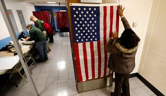 ** FILE ** Evelyn Dennis hangs a U.S. flag as election workers set up voting booths at Memorial Elementary School in Little Ferry, N.J., on Nov. 6, 2012. (Associated Press)