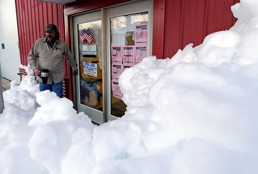 Snow surrounds the polling precinct in Terra Alta, W.Va., as Peter Hough heads to work after casting his ballot on Election Day, Tuesday, Nov. 6, 2012. (AP Photo/Dave Martin)