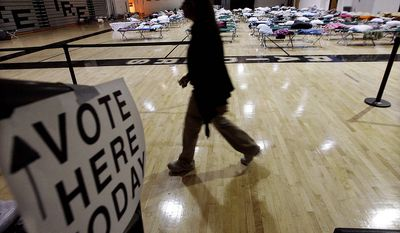 A person walks through a makeshift shelter in a gymnasium at Toms River East High School on the way to vote on Tuesday, Nov. 6, 2012, in Toms River, N.J.  Voter turnout was heavy in several storm-ravaged Jersey shore towns, with many voters expressing relief and even elation at being able to vote at all, considering the devastation. (AP Photo/Mel Evans)
