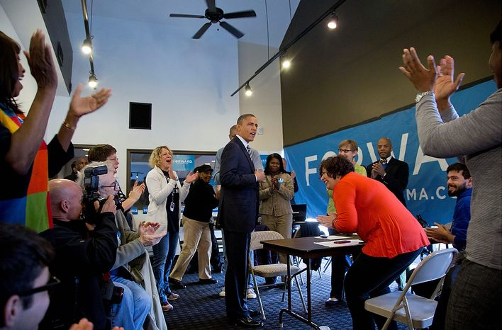 President Barack Obama is applauded as he visits with volunteers at a campaign office the morning of the 2012 election, Tuesday, Nov. 6, 2012, i