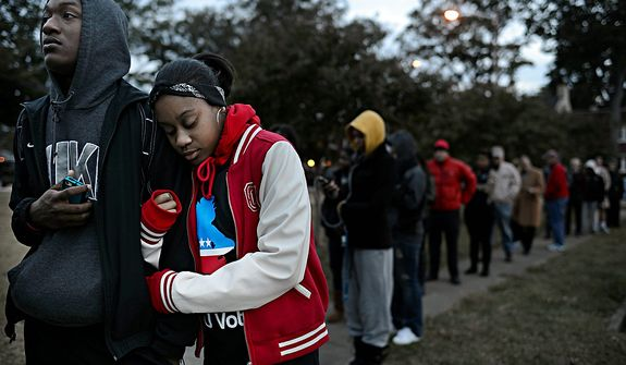 William Wright, left, and India Johnson, right, both freshman at ODU, wait on line  to vote at Larchmont Elementary School in Norfolk, Va. on Tuesday, Nov. 6, 2012. Wright and Johnson, both 18 and from Richmond, were excited to cast their first votes in the Presidential election. (AP Photo/The Virginian-Pilot, Amanda Lucier)