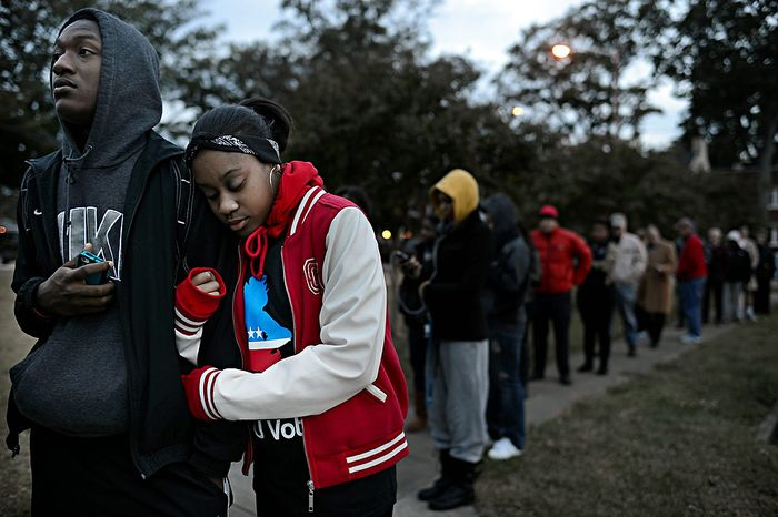 William Wright, left, and India Johnson, right, both freshman at ODU, wait on line  to vote at Larchmont Elementary School in Norfolk, Va. on Tuesday, Nov. 6, 2012. Wright and Johnson, both 18 and from Richmond, were excited to cast thei