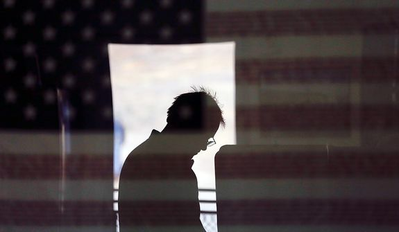 Hal Pigg casts his vote, reflected in an image of a flag, on Election Day Tuesday, Nov. 6, 2012, in Jamul, Calif. (AP Photo/Gregory Bull)