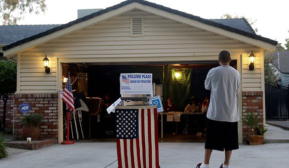 Dave Reyes II waits to be the first voter in his precinct outside of the polling station set up in the garage of the Gallegos residence in Stockton, Calif., Tuesday, Nov.  6, 2012. (AP Photo/Marcio Jose Sanchez)