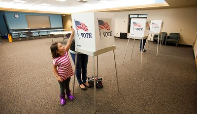 Baylee Hernandez, 4, plays next to her mother Britni Tortora, of Arvada, while she votes at the Apex Center Tuesday Nov. 6, 2012 in Arvada, Colo. (AP Photo/Barry Gutierrez)