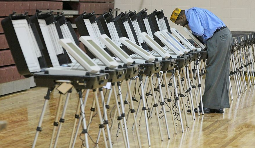 Poll Manager, Melvin Davis Jr. unlocks the voting machines  at Grady High School,  Tuesday, Nov. 6, 2012 in Atlanta. (AP Photo/Atlanta Journal-Constitution, John Spink)