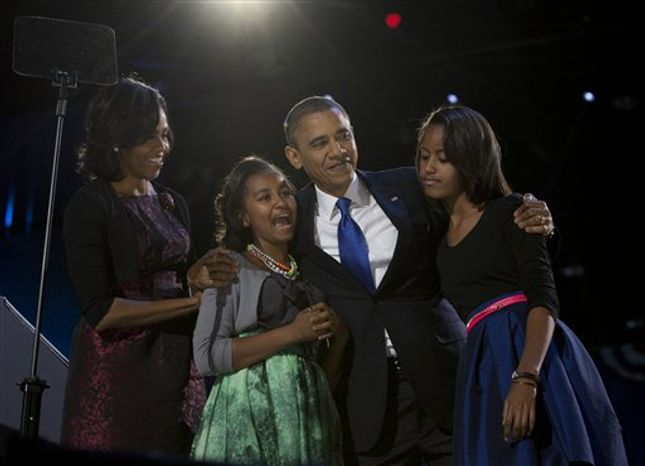 President Barack Obama, accompanied by first lady Michelle Obama and daughters Malia and Sasha arrive at the election night party Wednesday, Nov. 7, 2012, in Chicago. Obama defeated Republican challenger former Massachusetts Gov. Mitt Romney. (AP Photo/Carolyn Kaster)