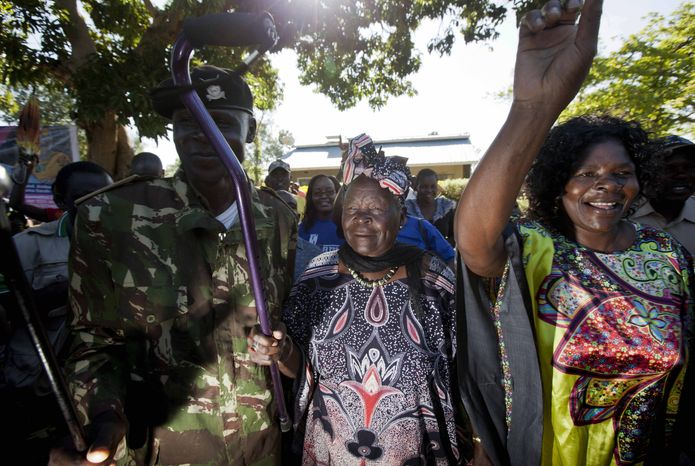 Sarah Obama, step-grandmother of President Barack Obama, waves her walking cane in the garden of her house in the village of Kogelo, Kenya, towards supporters in celebration Nov. 7, 2012, before speaking to the media about her reaction to Obama's re-election in the U.S. presidential election. (Associated Press)
