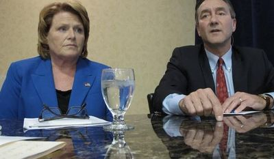 **FILE** Democratic U.S. Senate candidate Heidi Heitkamp (left) listens to Republican opponent Rick Berg speak at a North Dakota Chamber of Commerce forum on health care and energy at a hotel in Bismarck, N.D., on Oct. 11, 2012. (Associated Press)