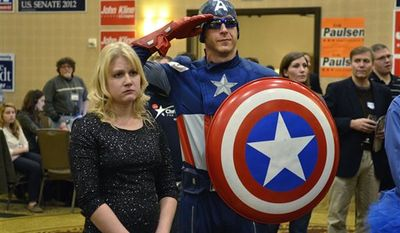 """Jon """" Captain America"""" Angell salutes as Republican Presidential candidate Mitt Romney concedes the election to Democratic Presidential candidate Barack Obama at the Minnesota Republican election headquarters, Tuesday, Nov. 6, 2012, in Bloomington, Minn. (AP Photo/Tom Olmscheid)"""