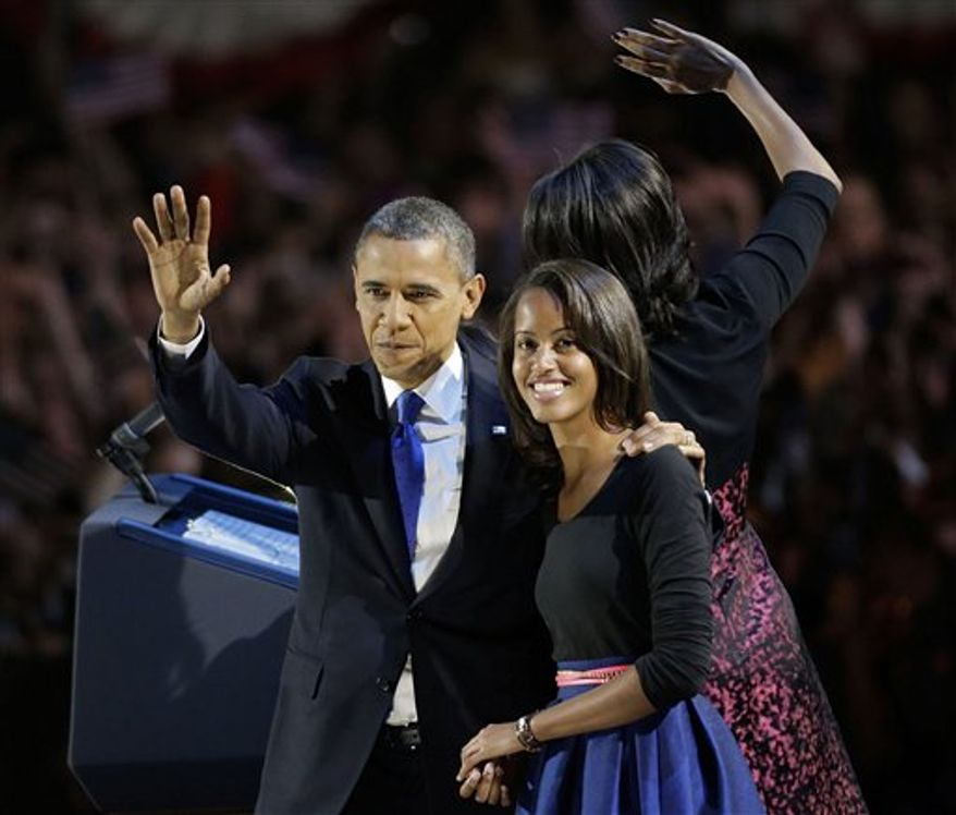 President Barack Obama, with his daughter Malia wave toward the crowd at his election night party Wednesday, Nov. 7, 2012, in Chicago. President Obama defeated Republican challenger former Massachusetts Gov. Mitt Romney. (AP Photo/Charles Rex Arbogast)