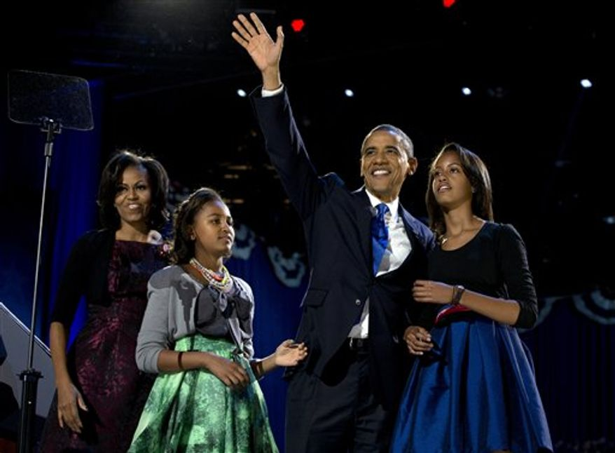 President Barack Obama waves as he walks on stage with first lady Michelle Obama and daughters Malia and Sasha at his election night party Wednesday, Nov. 7, 2012, in Chicago. Obama defeated Republican challenger former Massachusetts Gov. Mitt Romney. (AP Photo/Carolyn Kaster)