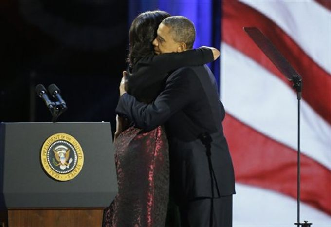 President Barack Obama kisses his wife Michelle as he walks out to the stage at his election night party Wednesday, Nov. 7, 2012, in Chicago. President Obama defeated Republican challenger former Mass