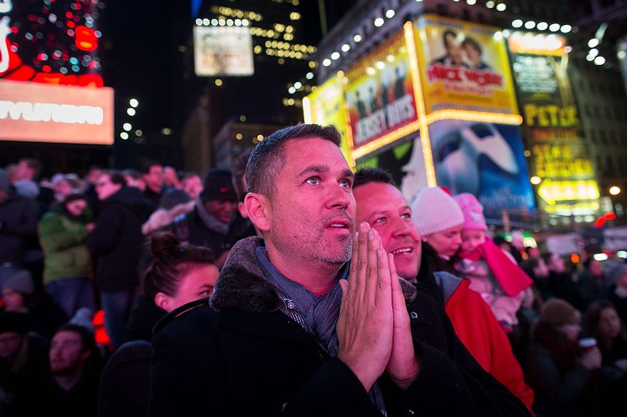 Cean Orrett, 45, center, and Gareth Edmondson-Jones, 46, of San Diago, both recently married in New York, react to positive predictions for President Barack Obama as crowds watch election results in Times Square, Tuesday, Nov. 6, 2012, in New York. After a year of campaigning, polls have begun to close after Americans across the United States headed to the polls to decide the winner of the tight presidential race between President Barack Obama and Republican presidential candidate, former Massachusetts Gov. Mitt Romney. (AP Photo/ John Minchillo)
