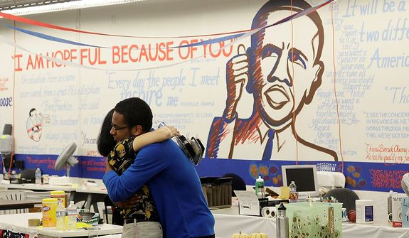 Volunteer Tyller Williamson, right, hugs Barbara Koh, Organizing for America California San Francisco department office manager, after projected returns of the presidential race were announced at the OFACSF Obama campaign volunteer office in San Francisco, Tuesday, Nov. 6, 2012. (AP Photo/Jeff Chiu)