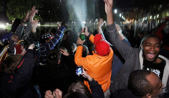 President Barack Obama supporters celebrate with champagne outside of the White House in Washington following his re-election early Wednesday, Nov. 7, 2012.  (AP Photo/Jose Luis Magana)