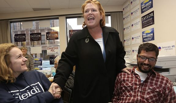 Democratic U.S. Senate candidate Heidi Heitkamp, center, talks as she greets elections volunteers Stef Claus, left, and Matt Traylor in Fargo, N.D, Tuesday, Nov. 6, 2012.  Heitkamp is running against Republican Rick Berg for the North Dakota's U.S Senate seat. (AP Photo/LM Otero)