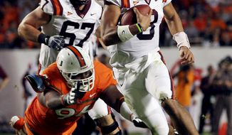 Miami's Curtis Porter (96) is unable to stop Virginia Tech quarterback Logan Thomas (3) during the first half of their NCAA college football game in Miami, Thursday, Nov. 1, 2012. (AP Photo/J Pat Carter)
