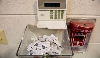 ** FILE** Voting tickets are collected near the exit door after each person finishes voting at Linwood Holton Elementary School on Election Day morning, Richmond, Va., Tuesday, Nov. 6, 2012. (Andrew Harnik/The Washington Times)