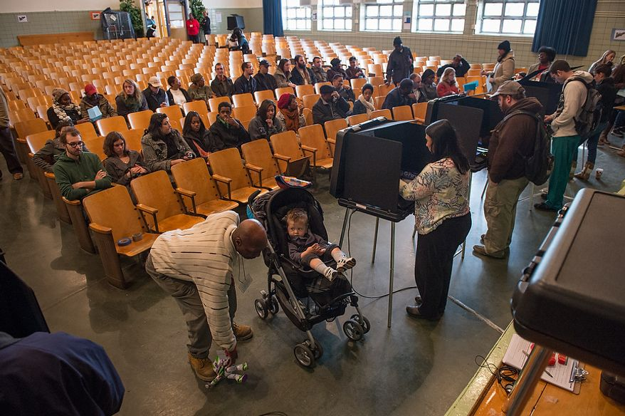 A poll worker picks up a toy dropped by Maxwell Macario [cq], 2, center, as he waits for his grandmother Laura Macario [cq], third from right, to vote in the auditorium at G.W. Carver Elementary School on election day morning, Richmond, Va., Tuesday, November 6, 2012. (Andrew Harnik/The Washington Times)