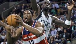 Washington Wizards forward Kevin Seraphin (13) drives to the basket past Boston Celtics forward Kevin Garnett during the first half of an NBA game in Boston on Wednesday, Nov. 7, 2012. (AP Photo/Elise Amendola)