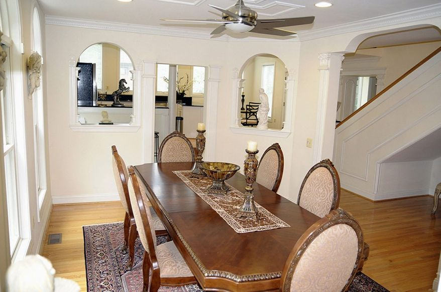 The dining room features two walls of windows and an arched entry from the hall.