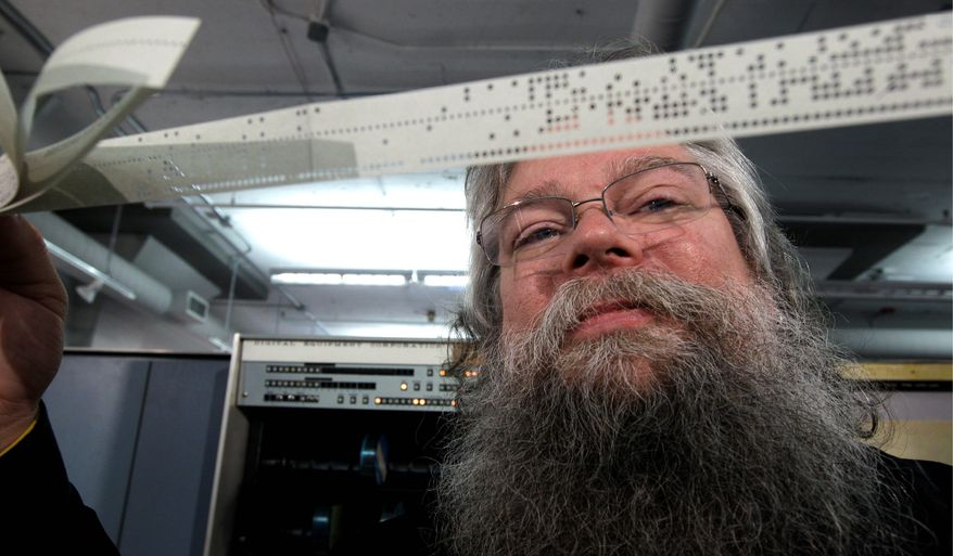 In this photo taken Oct. 30, 2012, Ian King, senior vintage systems engineer at the Living Computer Museum in Seattle, holds a strip of paper tape that is used to run a DEC PDP-7 computer from the mid 1960s, one of the oldest running computers at Paul Allen's newly opened Living Computer Museum, which features working models of old computers. (AP Photo/Ted S. Warren)