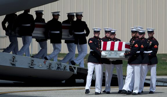 ** FILE ** Carry teams move transfer cases of the remains of the four Americans killed in Benghazi, Libya, from a transport plane during a ceremony Sept. 14, 2012, at Andrews Air Force Base, marking the start of congressional and State Department inquiries into the attack on the U.S. Consulate in Benghazi. (Associated Press)