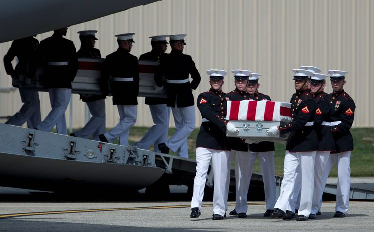 ** FILE ** Carry teams move transfer cases of the remains of the four Americans killed in Benghazi, Libya, from a transport plane during a ceremony Sept. 14, 2012, at Andrews Air Force Base, marki