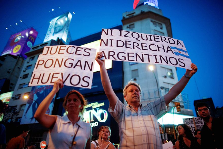 "People hold banners reading in Spanish ""Not right nor left, Argentines"" and ""Judges get some balls"" during an anti government demonstration in Buenos Aires, Argentina.  Thousands of people marched against rising inflation, crime, exchange controls and to express their fear to a constitutional reform that could open the way for a third consecutive reelection of Argentina's President Cristina Fernandez. (AP Photo/Natacha Pisarenko)"