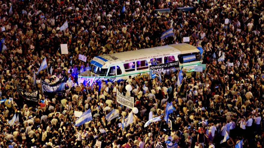 A vehicle is surrounded by protesters demonstrating during a march against Argentina's President Cristina Fernandez in Buenos Aires, Argentina.  (AP Photo/Natacha Pisarenko)