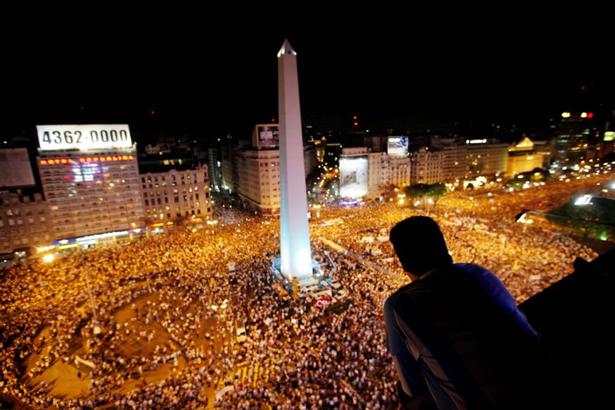 A man watches as protesters demonstrate during a march against Argentina's President Cristina Fernandez in Buenos Aires, Argentina, Thursday, Nov. 8, 2012. Angered by rising inflation, violent crime and high-profile corruption, and afraid Fernandez will try to hold onto power indefinitely by ending constitutional term limits, the protesters banged pots and marched on the iconic obelisk in Argentina's capital. Protests also were held in plazas nationwide and outside Argentine embassies and consulates around the world. (AP Photo/Natacha Pisarenko)