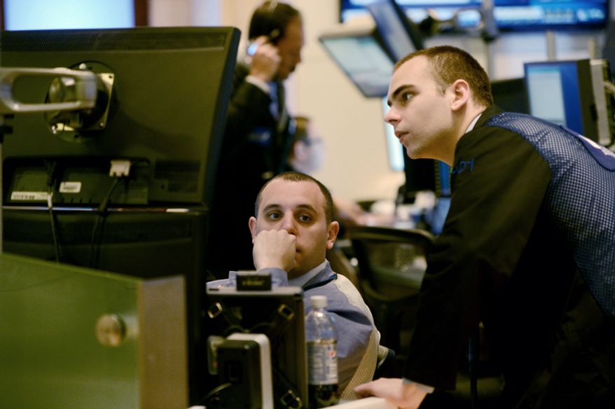 "Traders work on the floor of the New York Stock Exchange on Nov. 7, 2012, the day after President Obama was re-elected. U.S. investors dumped stocks and turned their focus to a world of problems, including a ""fiscal cliff"" of tax increases and spending cuts at home and a deepening recession in Europe. (Associated Press)"