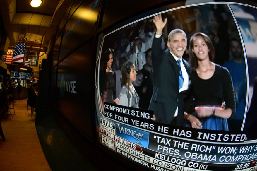 """A television feed on the floor of the New York Stock Exchange shows President Obama (left) and his daughter, Malia, on Nov. 7, 2012, the day after he was re-elected. U.S. investors dumped stocks and turned their focus to a world of problems, including a """"fiscal cliff"""" of tax increases and spending cuts at home and a deepening recession in Europe. (Associated Press)"""