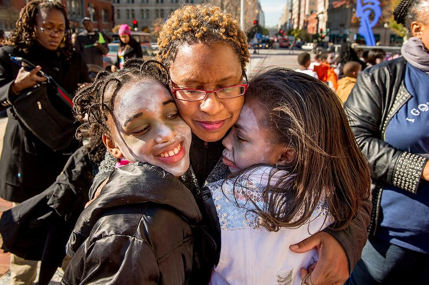 "Taylor Keys, 10, left, and Makayla Monk, 10, right, get a hug from third grade teacher Ms. Odem after the girls and other students with Savoy Elementary School perform a flash mob dance to Michael Jackson's ""Thriller"" in front of the National Portrait Gallery as a way to teach music theory, movement and the impact of the song on the music industry and the ""cultural fabric of our society,"" Washington, D.C., Thursday, November 8, 2012. (Andrew Harnik/The Washington Times)"