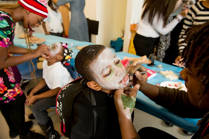 "Savoy Elementary School students Hope Brown, 7, second from left, and Deshean Dean, 9, center, get their makeup done by Rechelle Rice, left, and Otisi Okiyi Jr., right, both part time art program assistants before students perform a flash mob dance to Michael Jackson's ""Thriller"" in front of the National Portrait Gallery as a way to teach music theory, movement and the impact of the song on the music industry and the ""cultural fabric of our society,"" Washington, D.C., Thursday, November 8, 2012. (Andrew Harnik/The Washington Times)"