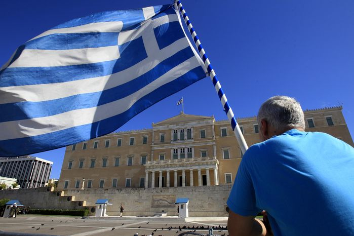 ** FILE ** A protester holding a Greek flag looks at the Greek Parliament in Athens on Tuesday, Nov. 6, 2012. Greece's unions are holding their third general strike in six weeks to press dissenters in the country's troubled coalition government not to back a major new austerity program that will doom Greeks to further hardship in a sixth year of recession. (AP Photo/Nikolas Giakoumidis)