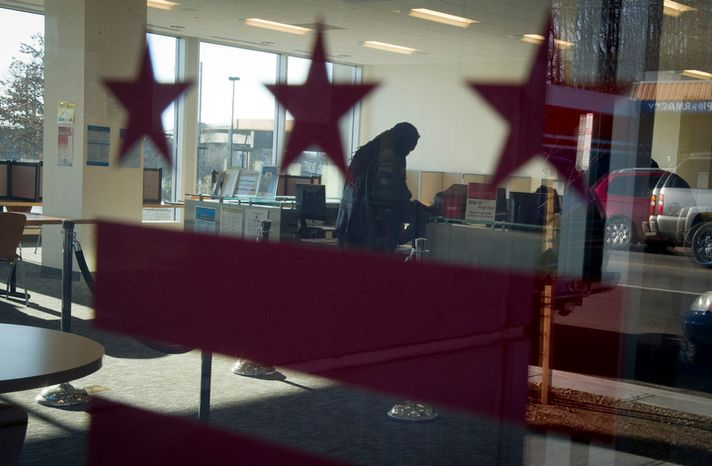 **FILE** An unidentified man gets assistance from a staff member at the Department of Employment Services office in D.C. on Feb. 6, 2012. (Rod Lamkey Jr./The Washington Times)