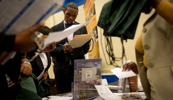 **FILE** James Carter, 30, an unemployed teacher's aide from Largo, Md., gathers information from the Beltsville Agricultural Research Center during the 2011 Career Fair at Prince George's Community College in Largo on Nov. 3, 2011. (Rod Lamkey Jr./The Washington Times)