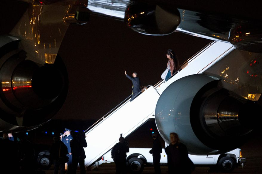 President Obama waves Nov. 7, 2012, as he exits Air Force One in Washington with first lady Michelle Obama and daughters Malia and Sasha on return to the White House after spending Election Night in Chicago. (Associated Press)