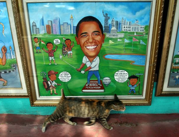 """A cat passes in front of a painting of President Obama at a roadside studio in Jakarta, Indonesia, on Nov. 8, 2012. The writing at left in the painting reads, """"Hope Mr. Obama does like to intervene in the sovereignty of other countries."""" The writing at right reads, """"Congratulations Mr. Obama. Hopefully the peace you are promoting is not only rhetoric."""" (Associated Press)"""