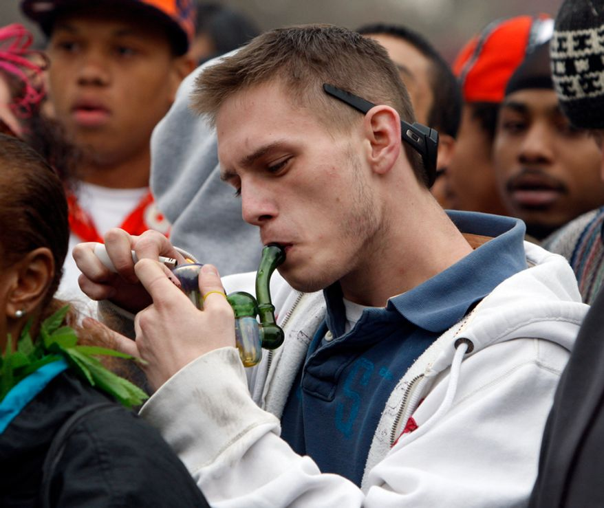 **FILE** An unidentified man lights up his pipe during a marijuana users rally at Civic Center Park across from the Capitol in Denver on April 20, 2010. Thousands of marijuana users gathered for the High Holiday, when pot users traditionally celebrate the drug, to urge Colorado to consider legalizing the drug for recreational use. (Associated Press)